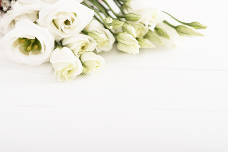 Bouquet of white roses on white wooden table, high key