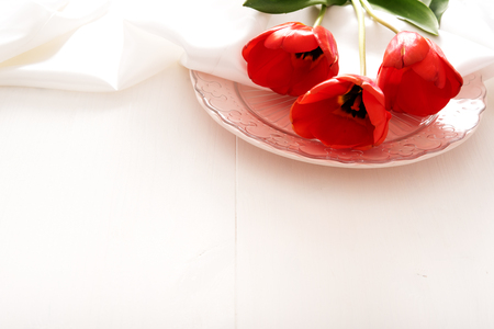Plate with red tulips on white wooden table