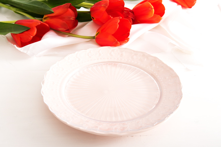 Empty plate and red tulips on white wooden table
