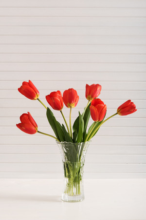 Colorful tulips in vase on white wooden table