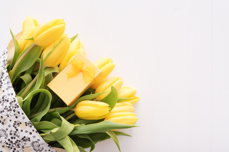 Colorful tulips with small gift box on white wooden table with copy space Imagens