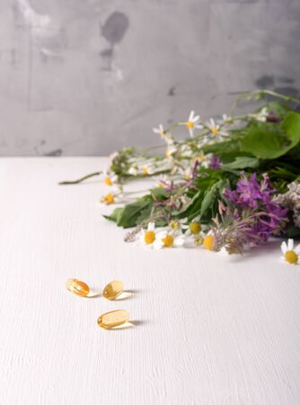 Armful of fresh medicinal plants on the table and yellow pills, daylight Standard-Bild