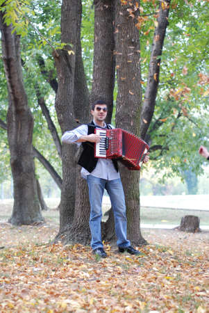 Man playing accordion in park photo