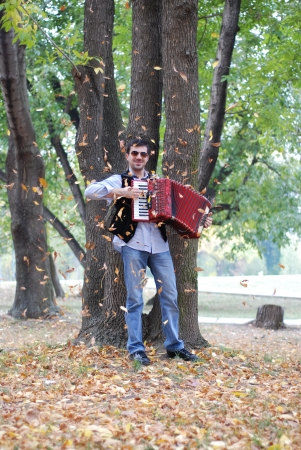 Man playing accoridion in park photo