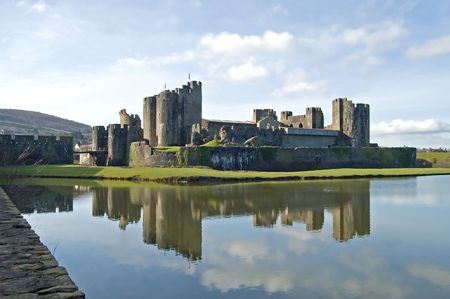 The medieval castle at Carephilly, Wales, reflected in its moat. Stock Photo