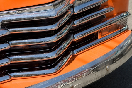 grille: Orange and chrome on the grille of this vintage car.