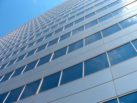 diagonally: Looking diagonally up the side of a skyscraper with clouds reflecting in the windows.