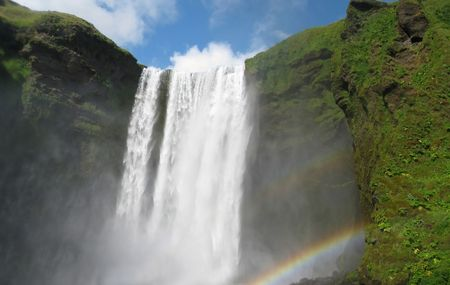 The tall waterfalls of Skogafoss, southern Iceland, complete with rainbow.