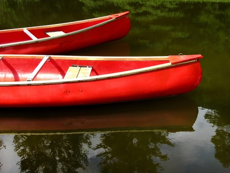 A pair of bright red canoes reflecting in the calm waters of a lake - waiting for customers. Stock Photo - 7452185