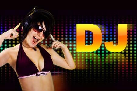 The young beautiful dj-girl dancing in a night club photo