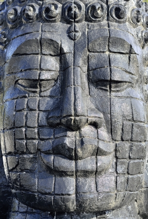 The face of a carved stone buddha
