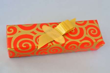 Anniversary gift wrapped in red and gold ribbon Stock Photo - 18144424