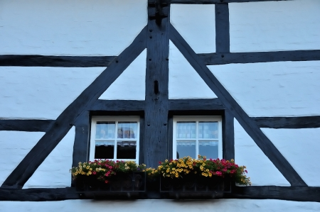 White windows of an old building with wooden beams on the fa