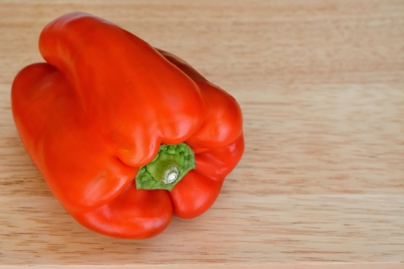 A raw red peppers with wooden background Stock Photo