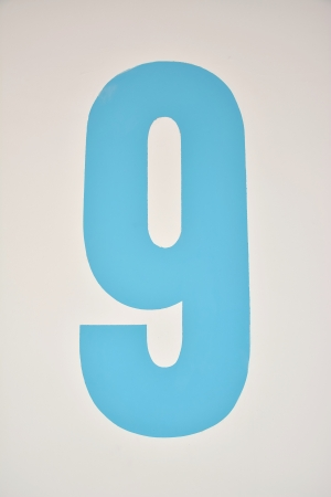 Number nine painted in blue on a wall