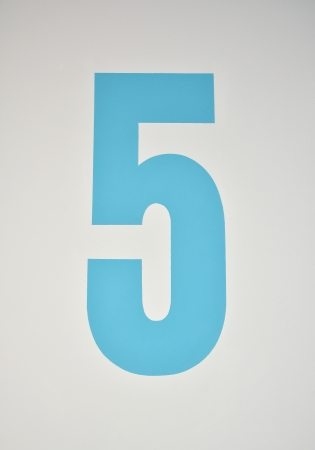 assigning: Number five painted in blue on a wall