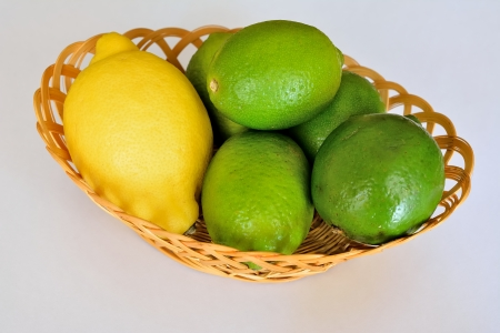 A wicker basket with limes and one lemon