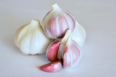 Four heads of garlic isolated on white