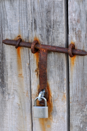 Detail of an old door and a lock latch and rusty again Stock Photo