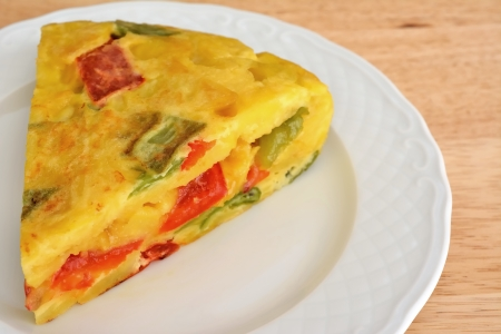 Portion of Spanish omelette with red and green peppers and onions on white plate Stock Photo