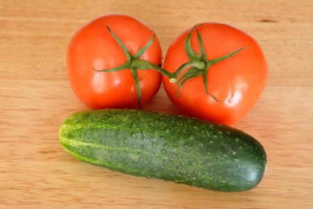 Image of two tomatoes and a cucumber with wood background