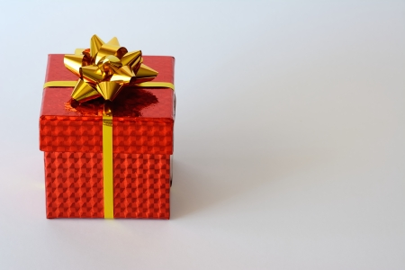 A bright red small box with golden ribbon and Christmas ornaments and white background