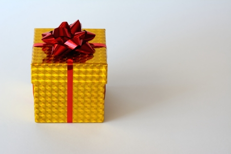 Small bright yellow box with ribbon and red ornament on white background