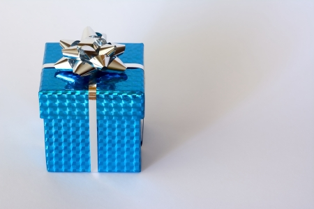 Blue box with silver ribbon and Christmas ornaments and white background Stock Photo
