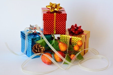 Three gift boxes decorated with Christmas motifs and a ribbon around Stock Photo