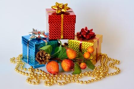 three gift boxes: Tres cajas de regalo decoradas con motivos de Navidad y collar de perlas de oro