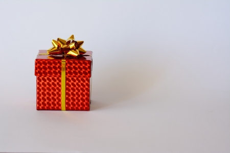 A bright red small box with golden ribbon and Christmas ornaments and white background photo