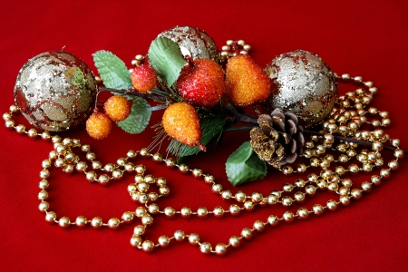 Christmas ornament decorated with objects, balls and gold necklace and red background
