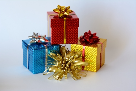 three brightly colored boxes with Christmas decoration and white background photo