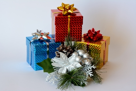 Three brightly colored boxes with decorative white themed Christmas