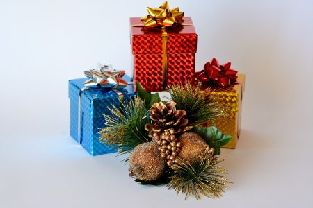 Three brightly colored boxes with Christmas ornaments and white background