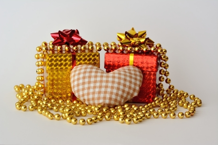 Two gift boxes, a heart and a pearl necklace with white background photo