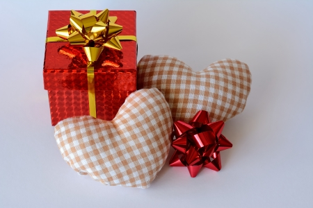 A red gift box, two hearts and white background photo