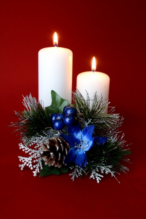 Two white candles with Christmas ornaments and red background
