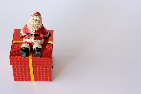 Red gift box with golden ribbon and santa claus