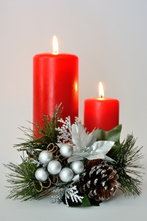 Two red candles with white and silver Christmas ornament