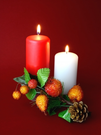 A white candle and a red with red background and Christmas ornament Stock Photo