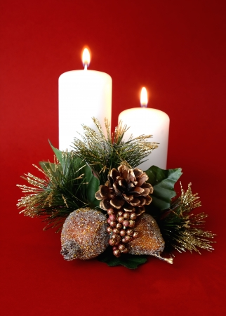 Two white candles with red background and Christmas ornament Stock Photo