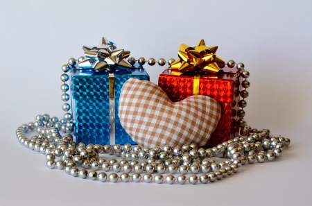 Two gift boxes a heart and a silver necklace with white background