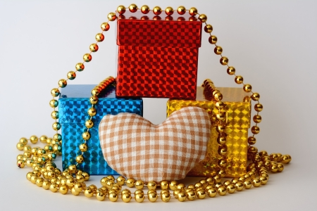 three gifts decorated with a heart and a golden necklace Stock Photo