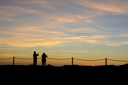 Silhouettes of a man and a woman photographing the sunset photo
