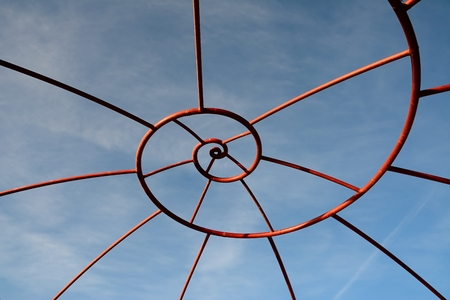 Shaped metal structure and spiral sky background Stock Photo