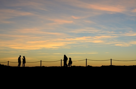Silhouettes of people walking by the sea with a beautiful sunset