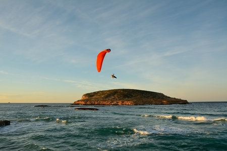 A man playing a sport flying above the sea, on an island Stock Photo
