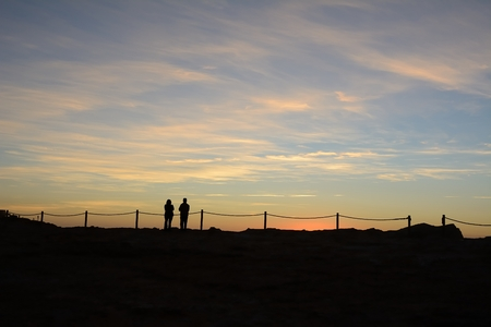 Two silhouettes of people watching the sunset