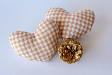 two hearts with white cloth and white checkered beige, and a Christmas ornament gold color